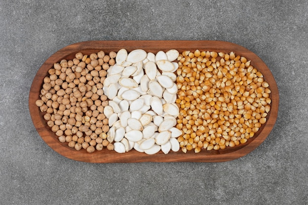 木の板においしいカボチャの種、トウモロコシの穀粒、エンドウ豆。