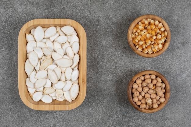 Gustosi semi di zucca, chicchi di mais e piselli su marmo.
