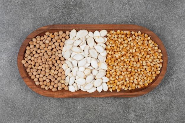 Gustosi semi di zucca, chicchi di mais e piselli sul piatto di legno.