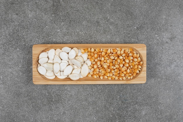 Gustosi semi di zucca e chicchi di mais sul piatto di legno.