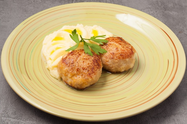 파슬리 잎으로 장식 된 버터와 치킨 커틀릿이 들어간 맛있는 퓨레