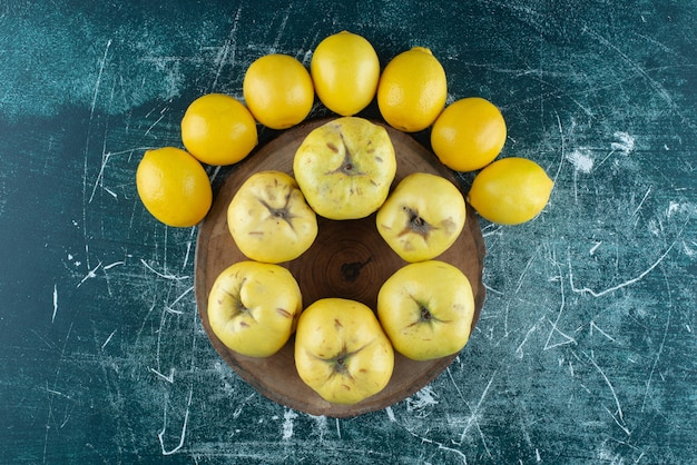 Tasty quinces and lemons on marble table.