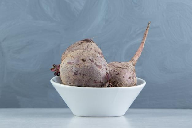 Вкусный редис в миске на мраморном фоне.