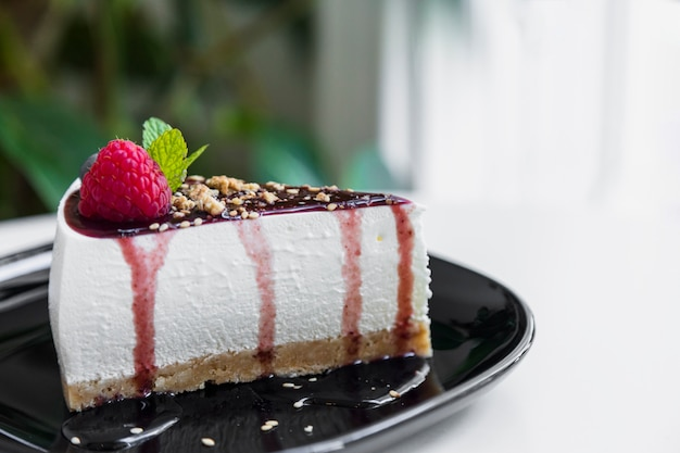 Tasty raspberry cheesecake slice with sauce on black ceramic