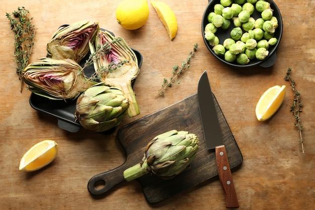 나무 테이블에 레몬과 브뤼셀 콩나물을 곁들인 맛있는 생 아티초크