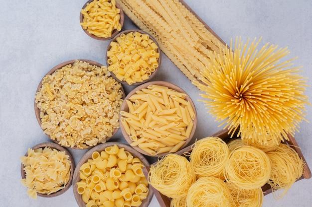 Gustosa pasta cruda e maccheroni su ciotole di legno