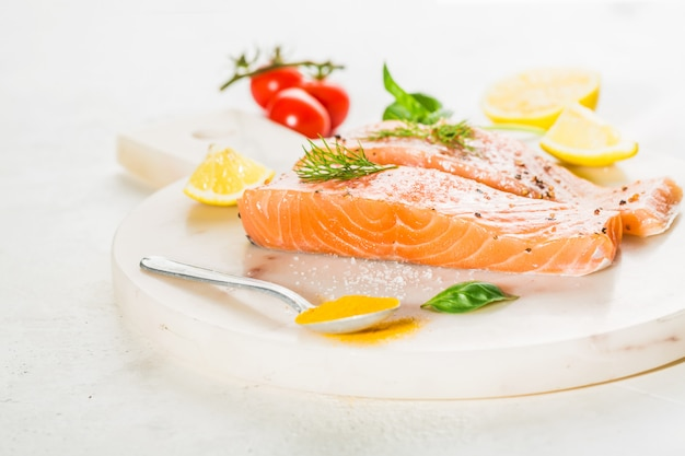 Tasty raw salmon steaks placed on board