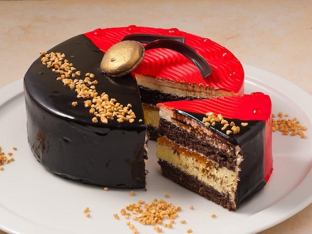 견과류와 스폰지 케이크와 함께 맛있는 빨간색과 검은 색 초콜릿 케이크