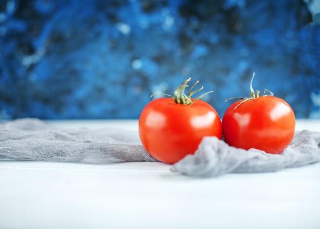 Вкусные красные помидоры на белом столе. еда и вегетарианство.