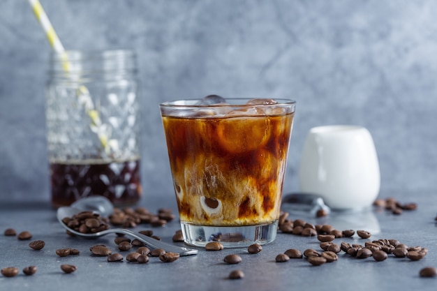 Tasty refreshing iced coffee with ice cubes in glasses on bright background. closeup