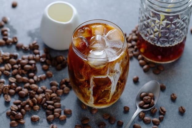 밝은 배경에 안경에 얼음 조각을 넣은 맛있는 상쾌한 아이스 커피. 확대