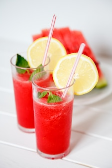 Tasty and refreshing watermelon juice with lemon and mint on white table