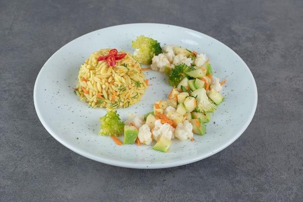 Вкусный рис и здоровые овощи на белой тарелке. фото высокого качества