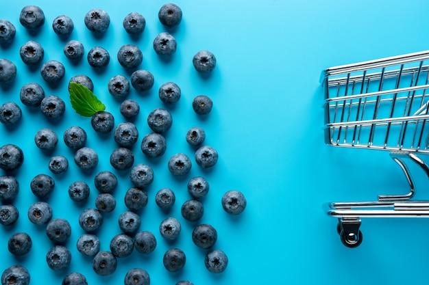 ショッピングカートで青い背景においしい熟したブルーベリー。