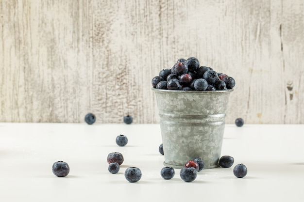Tasty ripe blueberries in a small metal bucket on white and grunge background, side view.