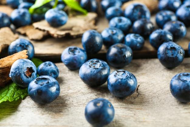 Вкусные спелые ягоды черники с зелеными листьями на деревянном столе крупным планом