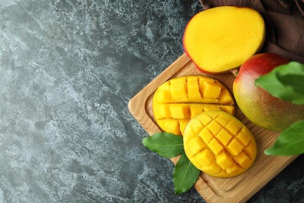黒いスモーキーテーブルの上のおいしい熟したマンゴーフルーツ