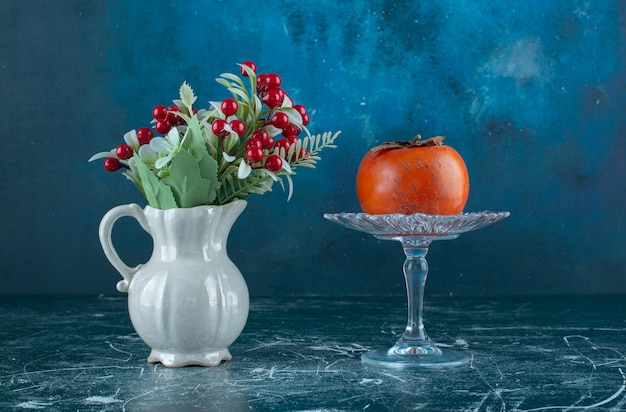 Tasty ripe persimmon on glass plate with vase of flowers.