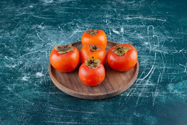 Tasty ripe persimmons on wooden plate.