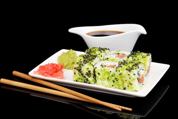 黒に分離された箸で白い皿においしいロールを提供