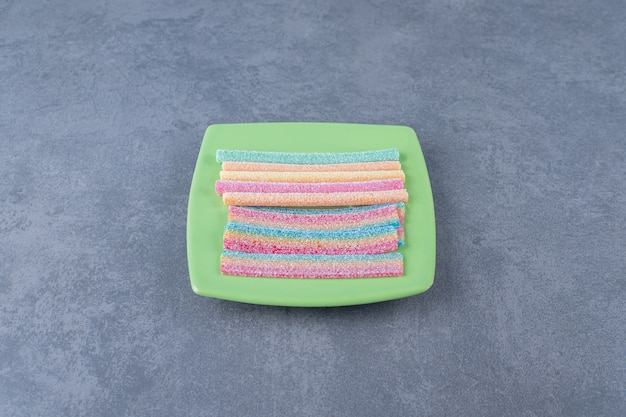Gustose caramelle a forma di corda su un piatto su un tavolo di marmo.