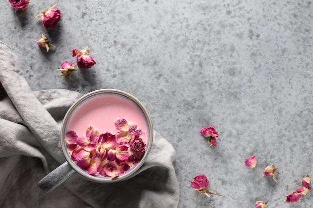 Вкусное розовое лунное молоко в серой чашке и лепестках роз на сером фоне. вид сверху. место для текста.