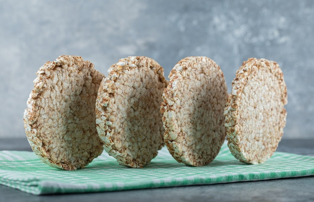 Tasty round rice cakes on striped tablecloth.