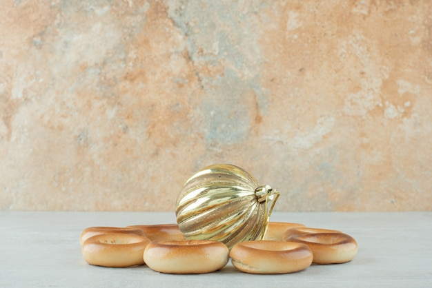白い背景に金色のクリスマスボールが付いたおいしい丸い甘いクッキー。高品質の写真