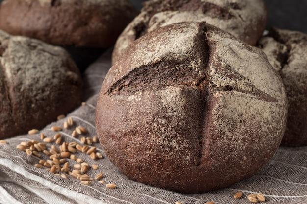Tasty rye buns on grey cloth, closeup
