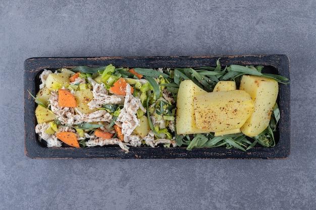 黒いプレートにおいしいサラダと茹でたジャガイモ。