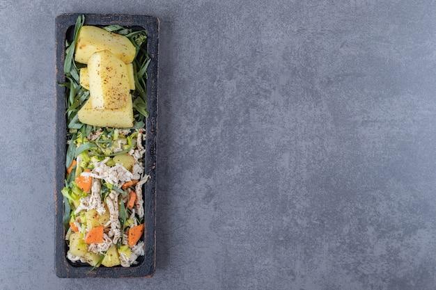 Вкусный салат и отварной картофель на черной тарелке.