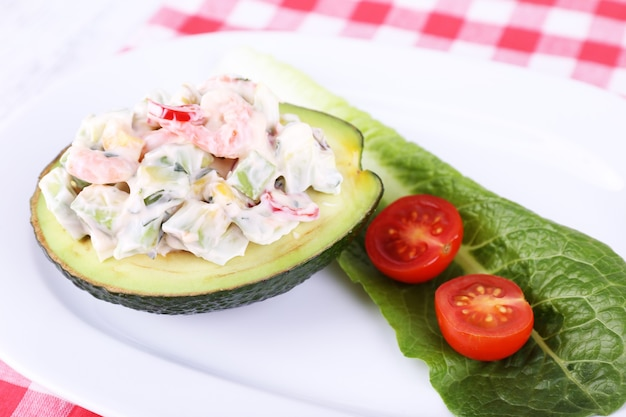 Tasty salad in avocado on plate close-up