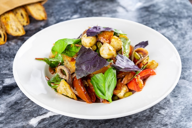 Tasty salad bowl with mozarella, vegetables, basil, spinach