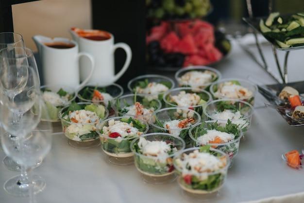 Вкусный салат в одноразовой посуде подается к столу на летней террасе в ресторанной концепции питания.