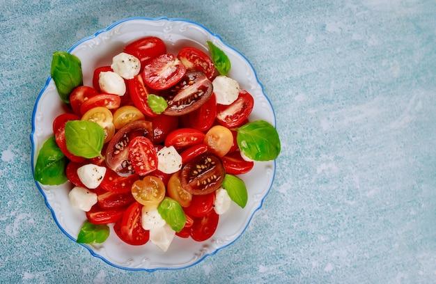 Вкусный салат из помидоров черри, сыра моцарелла и базилика на белой тарелке с вилкой. вид сверху.