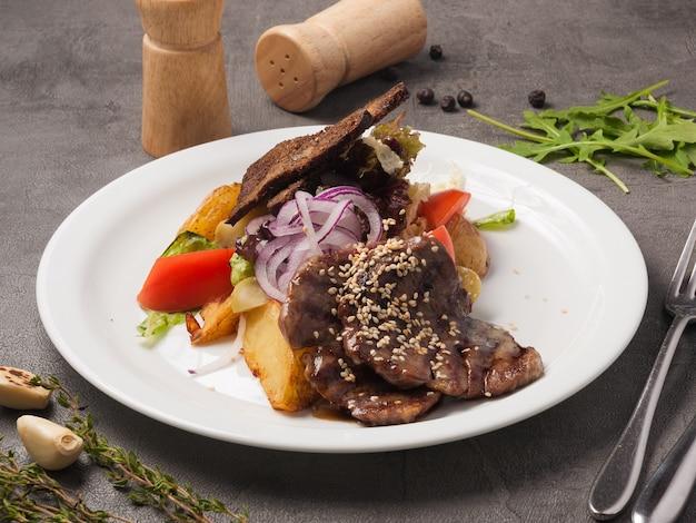 牛肉と野菜の照り焼きソースにゴマを添えたおいしいサラダ
