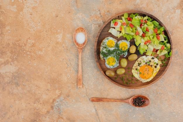木の板に卵を添えたおいしいサラダ。