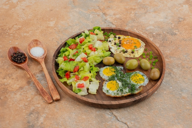 Tasty salad with eggs on wooden board .