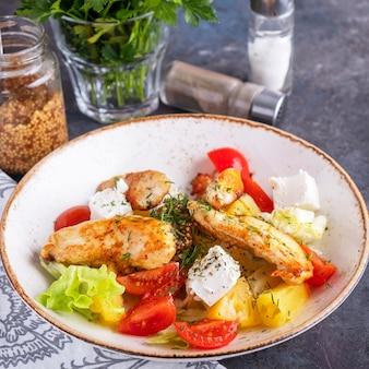 Вкусный салат с жареной курицей, помидорами, ананасом, сыром и листьями салата