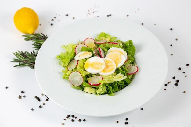 Вкусный салат с листьями салата, редисом и яйцом на белом