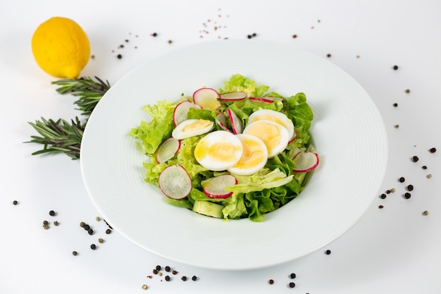 Tasty salad with lettuce radish and eggs on a white