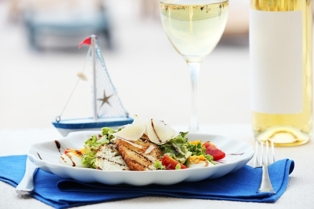 Tasty salad with served wine on blue napkin