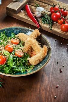 Вкусный салат с креветками в тесте kataifi в зеленой миске на деревянном столе. композиция с салатом, соусами, помидорами и розмарином. крупным планом зрения. еда плоская планировка