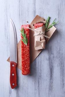 Вкусная колбаса салями, бумага на деревянном столе