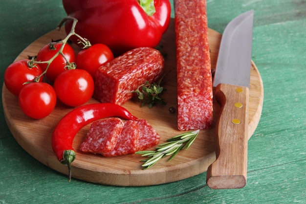 Tasty salami sausage and spices on wooden table