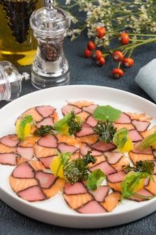해초로 장식 한 맛있는 연어와 훈제 참치 카르 파치 오