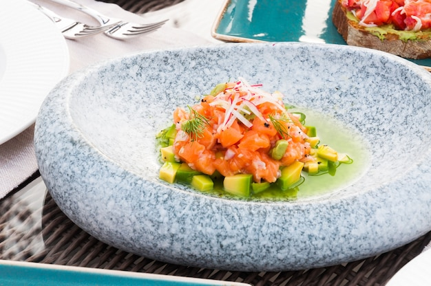 Вкусный тартар из лосося с авокадо в ресторане