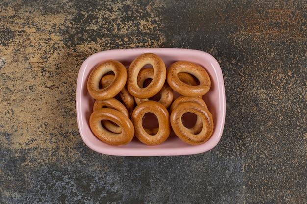 Вкусные соленые крекеры в розовой миске.