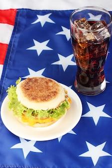 Вкусный бутерброд и стакан с колой, на американском флаге