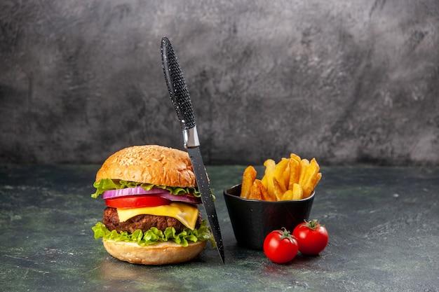 여유 공간이있는 어두운 혼합 색상 표면에 줄기가있는 맛있는 샌드위치와 나이프 튀김 토마토
